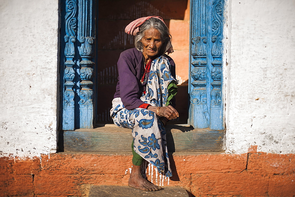 A old woman sits outside her house in Uttarakhand, India, Asia