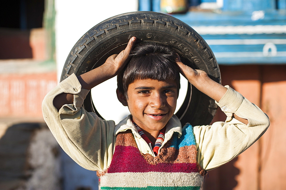 Children in India often utilise discarded wheels and turn them into toys, Uttarakhand, India, Asia