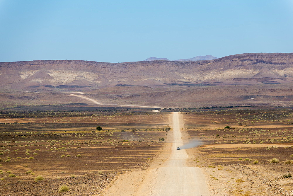 A 4x4 car leaves a cloud of dust as it apporachs along the long dusty road to the Fish River Canyon, Namibia, Africa