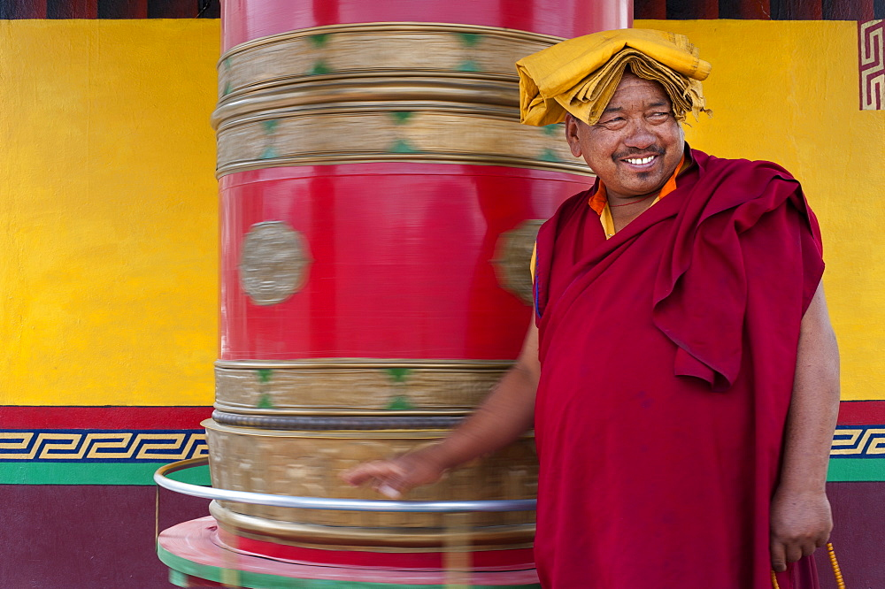 A Buddhist monk (lama) spins a prayer wheel at Diskit Monastery in the Nubra Valley, Ladakh, India, Asia