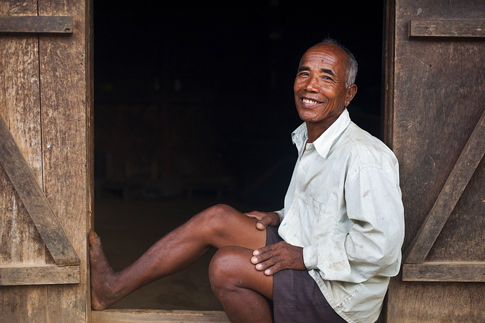 An old farmer sits in the doorway of his house, Meghalaya, India, Asia