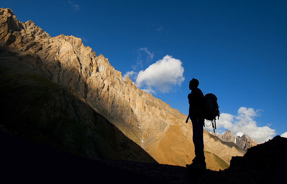 A trekker takes in the dramatic scenery from near the top of the Dung Dung La at 4710m during the Hidden valleys trek, Ladakh, India, Asia