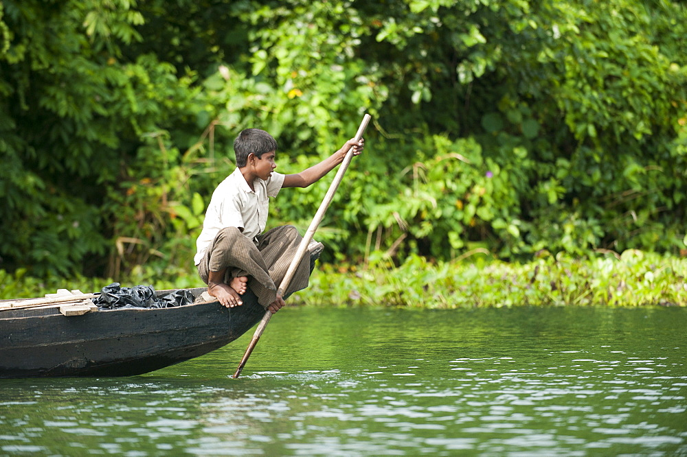 A boy paddles across Kaptai Lake, Chittagong Hill Tracts, Bangladesh, Asia