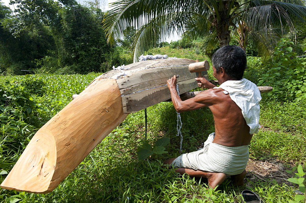 A man from Rangamati makes a traditional style dugout canoe, Chittagong Hill Tracts, Bangladesh, Asia