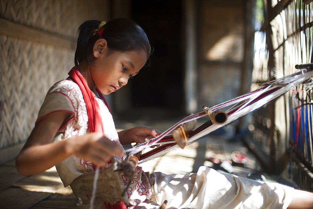 A little girl learns the skill of weaving on a handloom, Chittagong Hill Tracts, Bangladesh, Asia - 1225-875