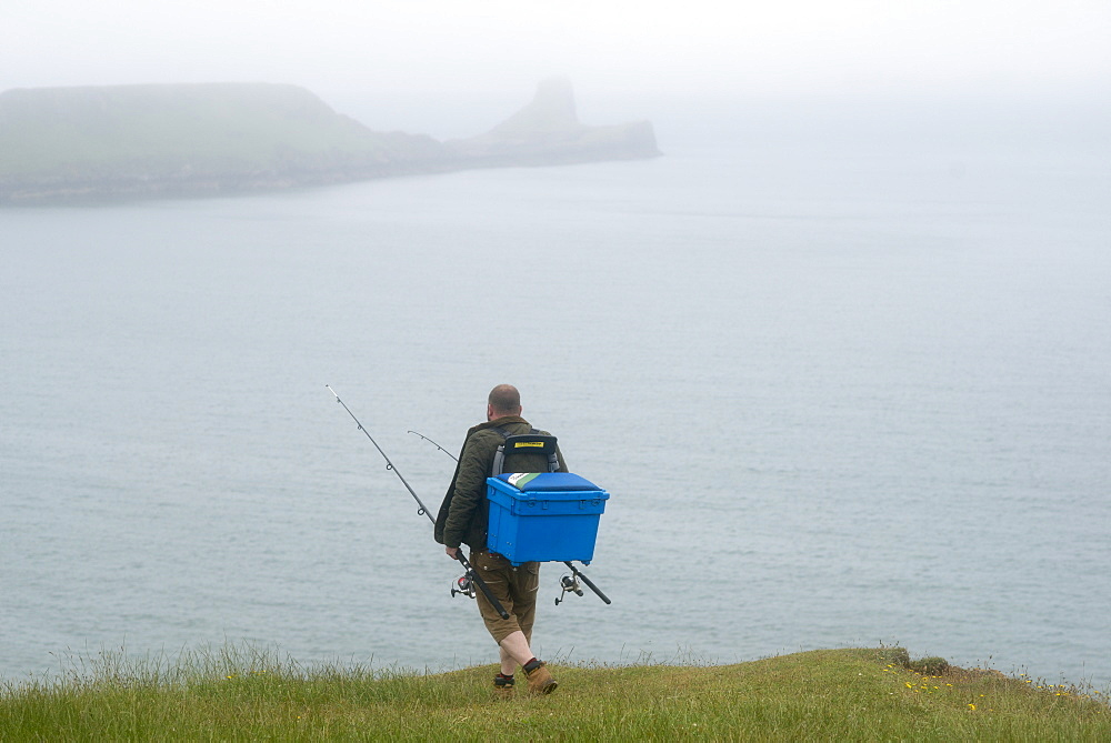 A fisherman walking towards Worms Head from Rhossili Bay on The Gower in South Wales, United Kingdom, Europe