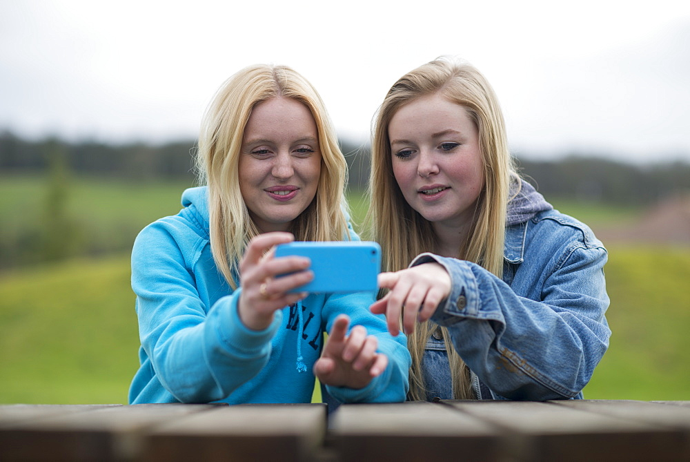 Girls reading a smartphone, England, United Kingdom, Europe