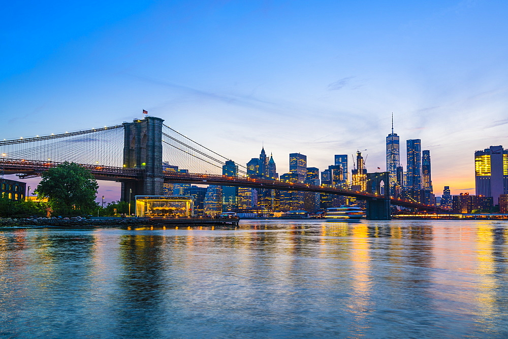 Brooklyn Bridge and Manhattan skyline at dusk, viewed from the East River, New York City, USA