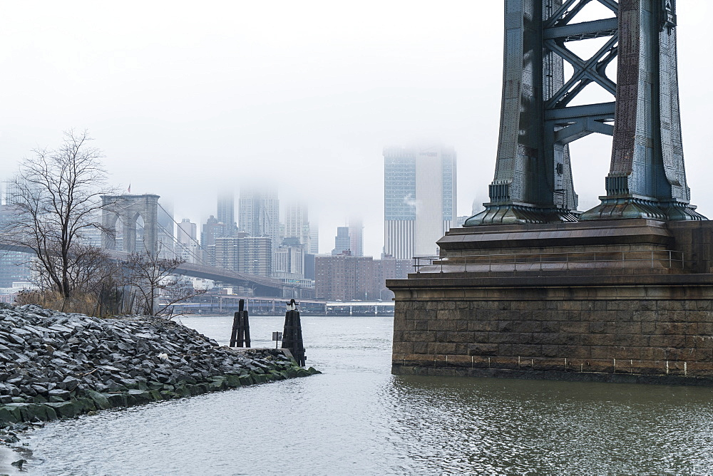 Manhattan Bridge on a cold foggy day, Brooklyn Bridge and skyline beyond, New York City, USA
