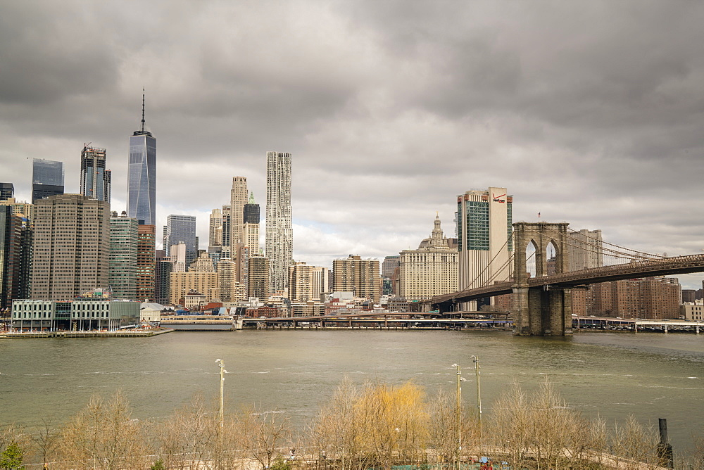 Manhattan skyline and Brooklyn Bridge on a cloudy day, New York City, USA