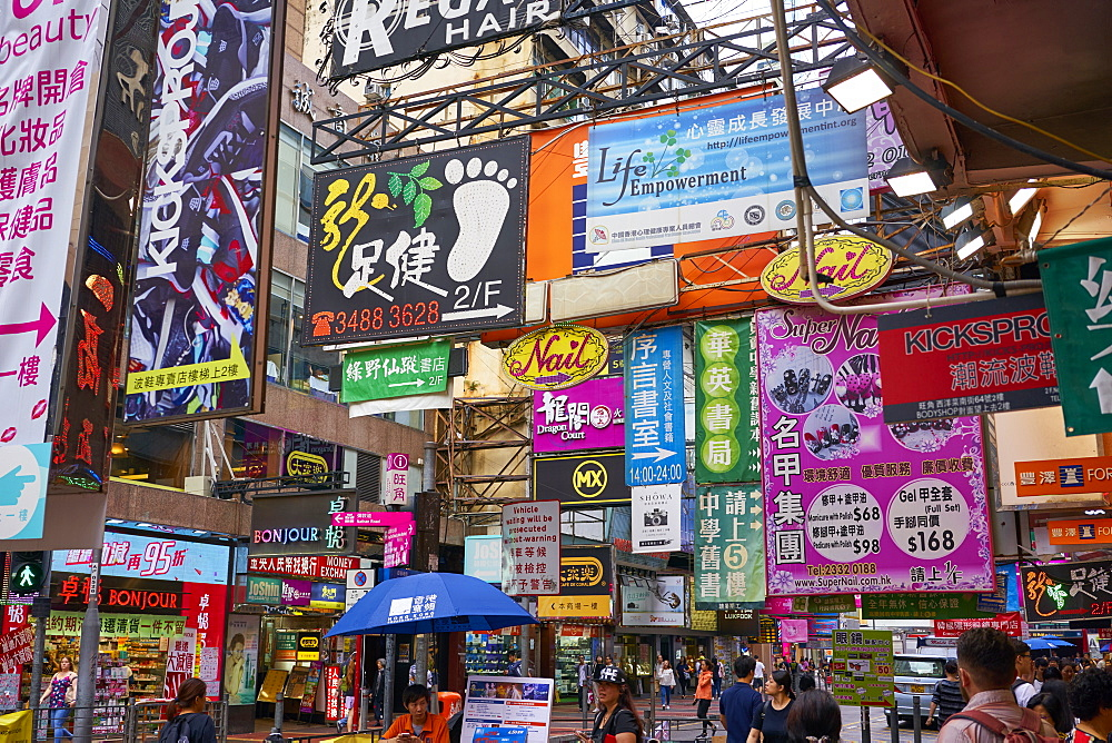 Advertising signs on a busy street in the popular shopping area of Mong Kok (Mongkok), Kowloon, Hong Kong, China, Asia