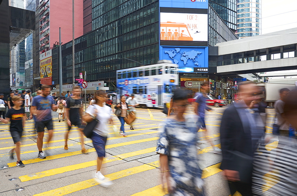 People crossing a busy road in Central, Hong Kong Island's busy shopping and business district, Hong Kong, China, Asia