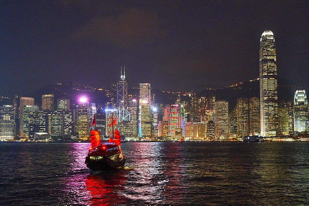 Traditional junk boat on Victoria Harbour with city skyline behind illuminated at night, Hong Kong