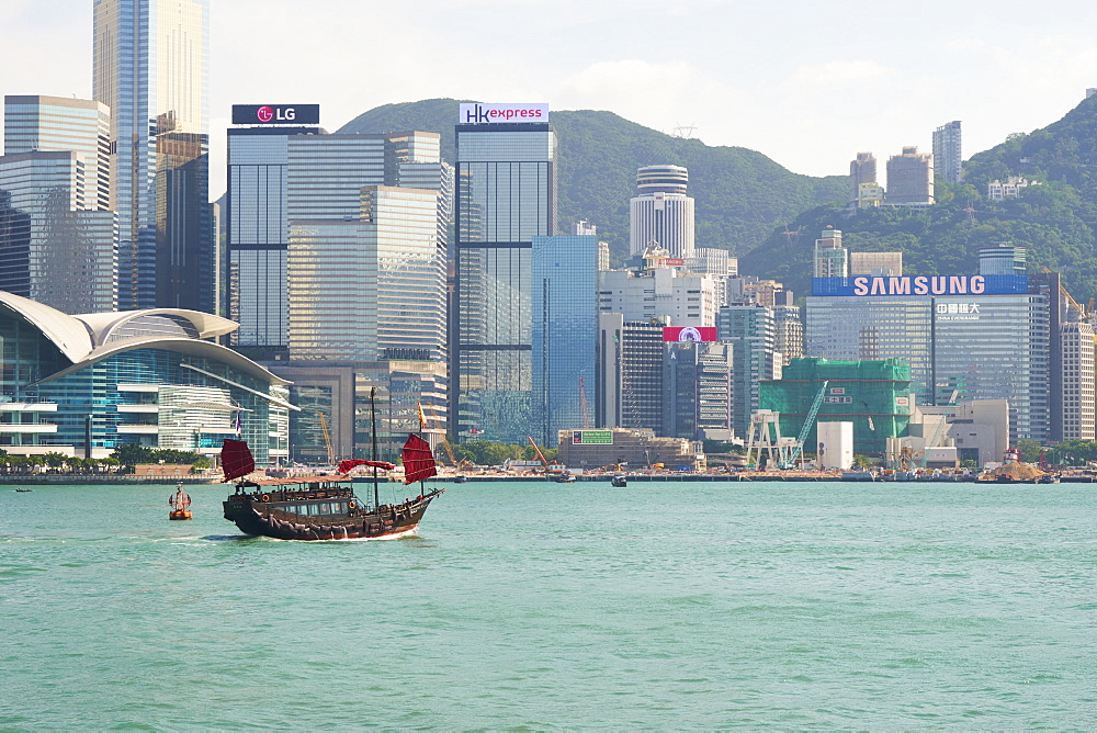 Traditional junk boat on Victoria Harbour with city skyline behind, Hong Kong, China, Asia