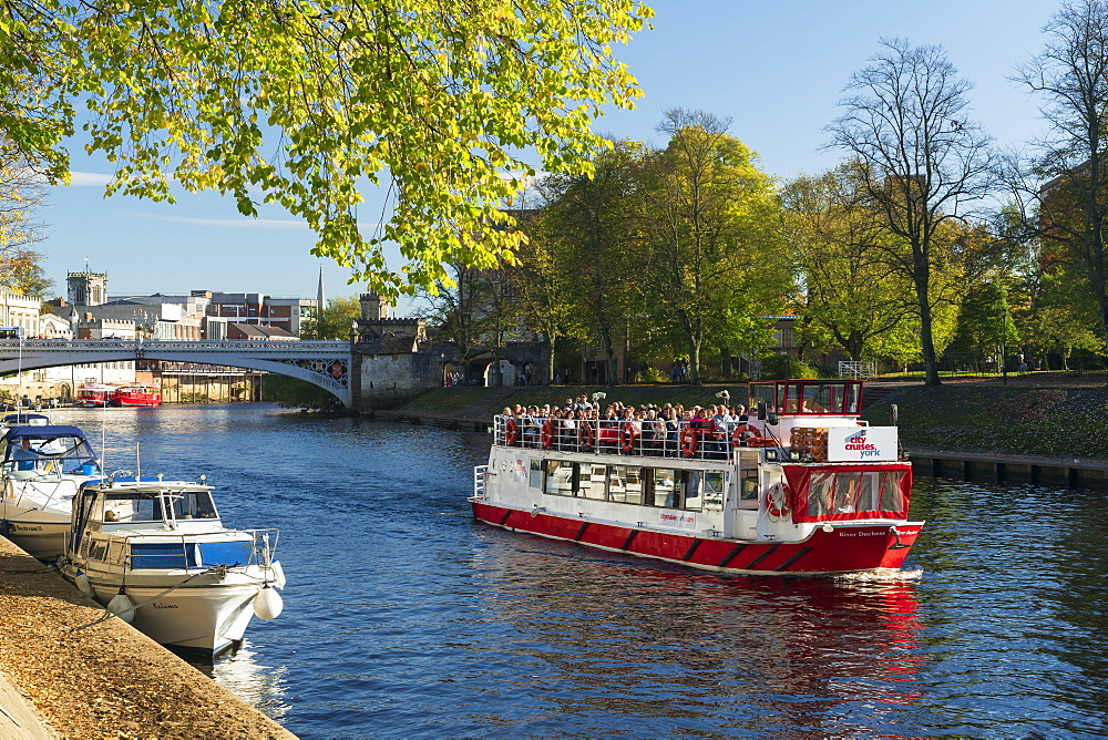Pleasure boats moored along the River Ouse and a York Boat full with tourists on a sightseeing river cruise.