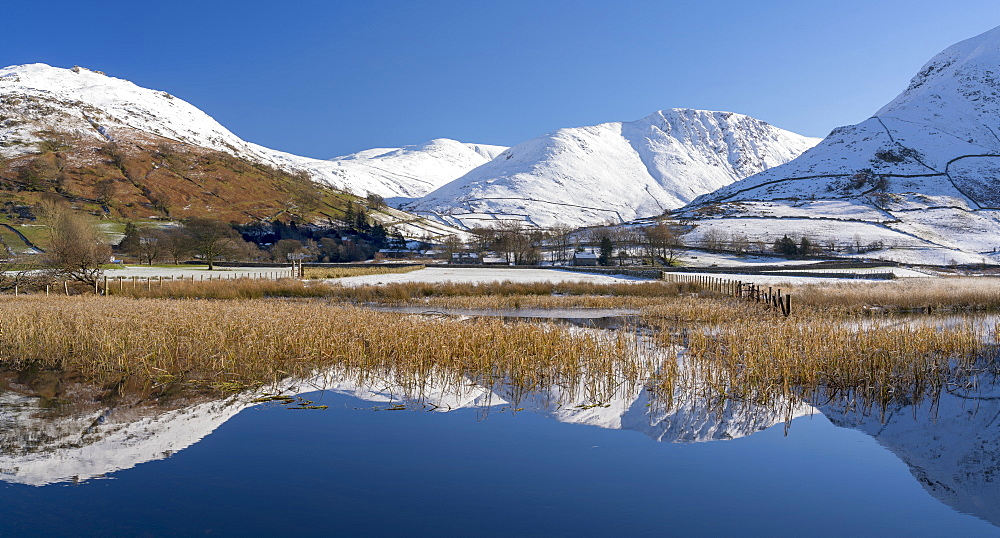 Snowclad sunlit fells around Hartstop reflected in Brothers Water, The English Lake District, UK>