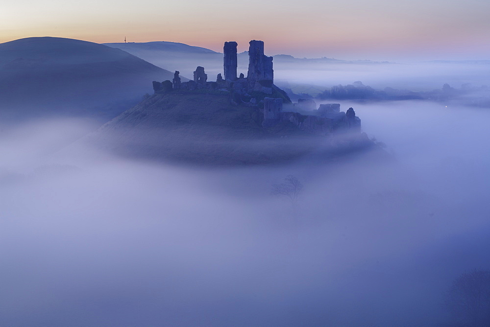 The ruins of Corfe Castle emerging from the mist before dawn on a spring morning, Corfe, Dorset, England, United Kingdom, Europe - 1229-4