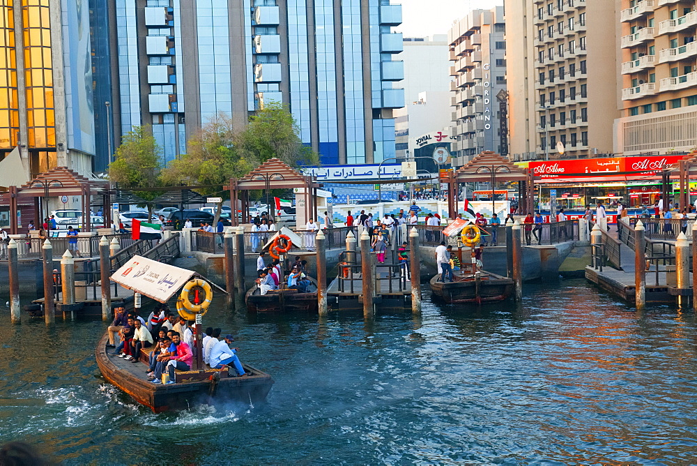 A water taxi carrying passengers arrives at a busy dock, Dubai Creek, Dubai, United Arab Emirates, Middle East