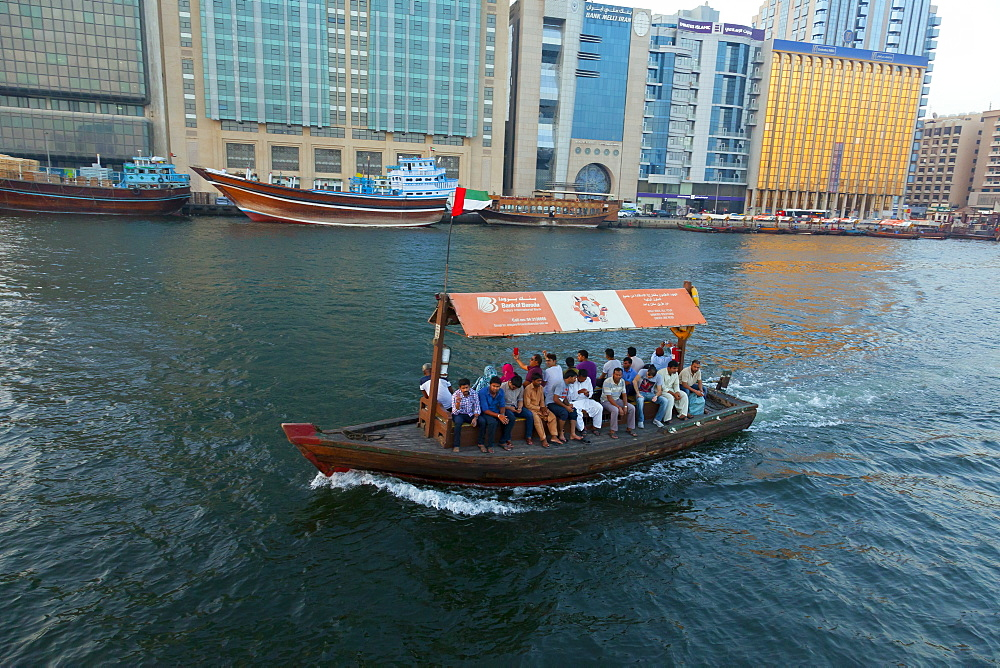A water taxi carries passengers across Dubai Creek, Dubai, United Arab Emirates, Middle East