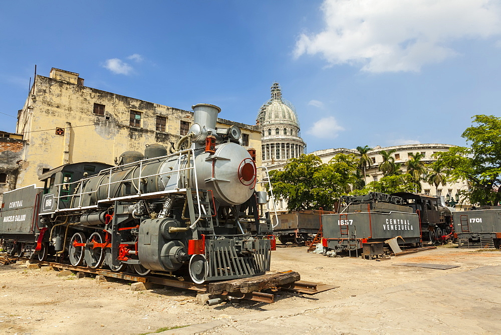 A vintage steam train in a restoration yard with the dome of the former Parliament Building in the background, Havana, Cuba, West Indies, Caribbean, Central America