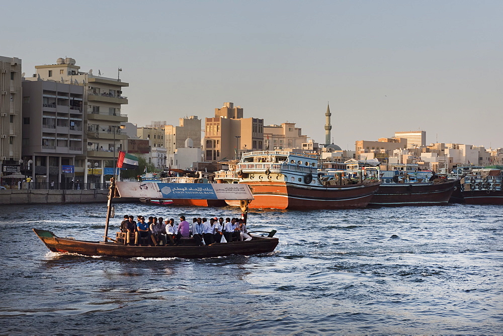 A water taxi carrying passengers crosses Dubai Creek, Dubai, United Arab Emirates, Middle East