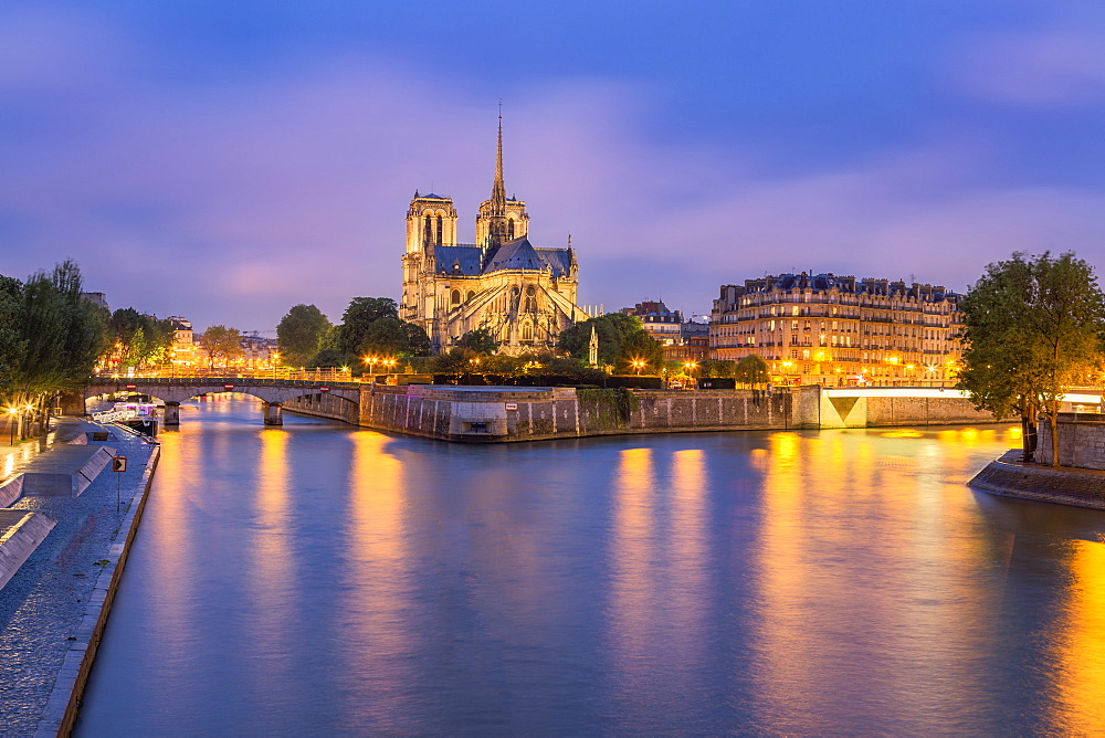 View of Notre Dame de Paris and its flying buttresses across the River Seine at blue hour, Paris, France, Europe