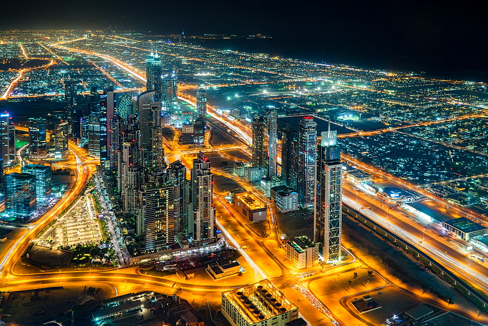 The streetlights and skyscrapers of Dubai are seen at night from high above the city.