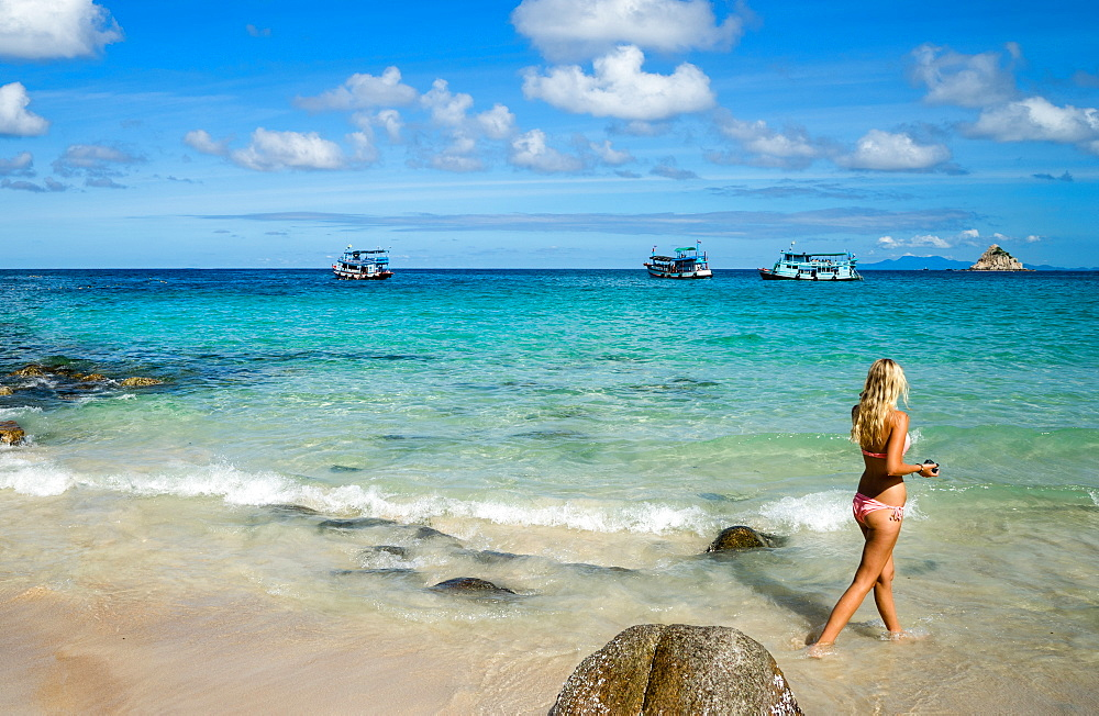 A woman in a bikini walks along a beach on Koh Tao, Thailand, Southeast Asia, Asia