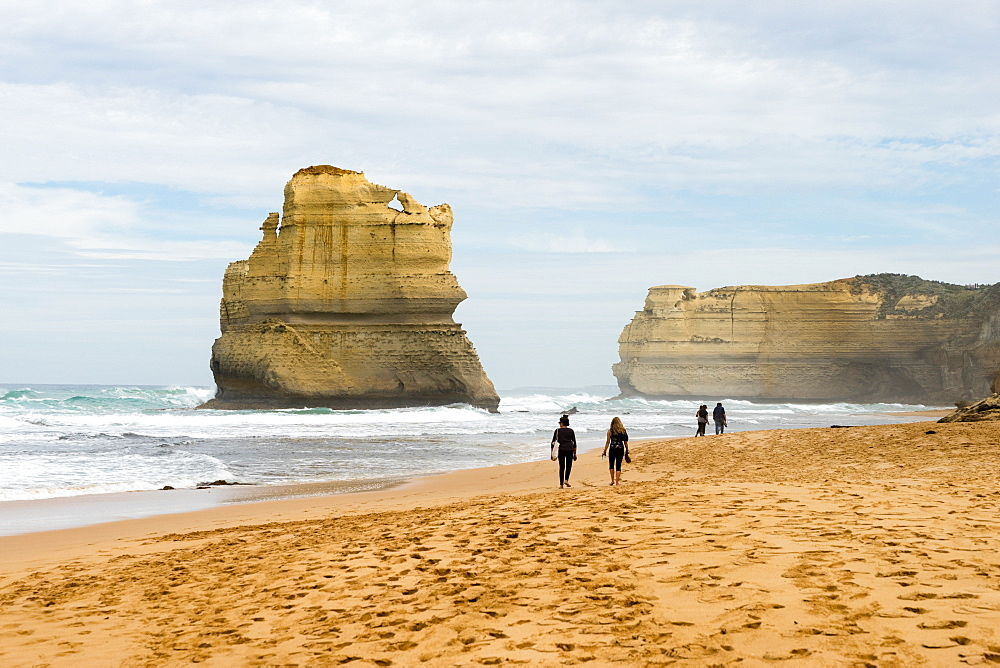 People walk along a beach with one of the Twelve Apostles geological formation in the background, Victoria, Australia, Pacific