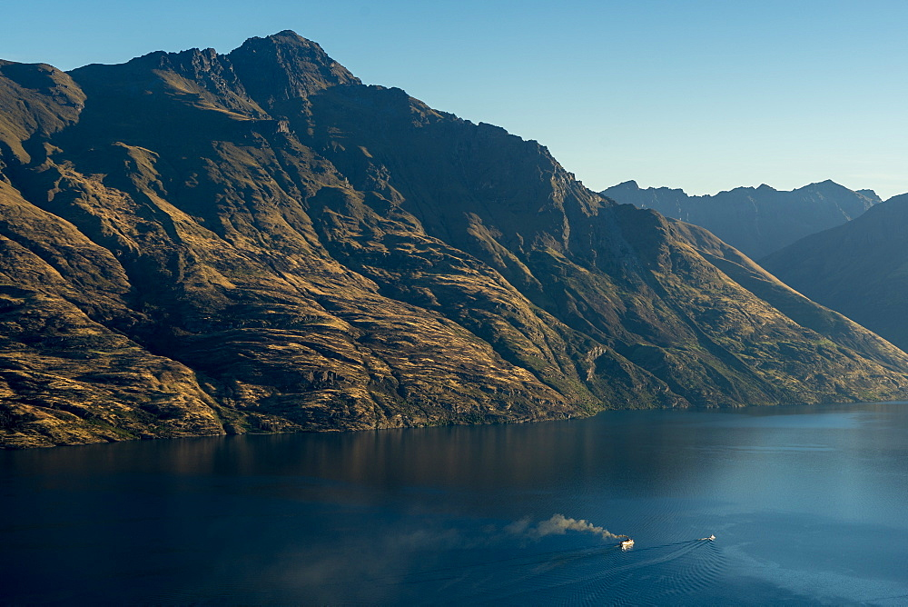 Steamship powers across a dark lake with sharp large mountains, Queenstown, Otago, South Island, New Zealand, Pacific