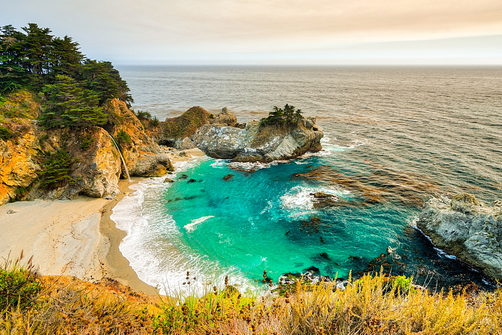 Smoky skies from a nearby wildfire turn the land orange at McWay falls in California, USA.