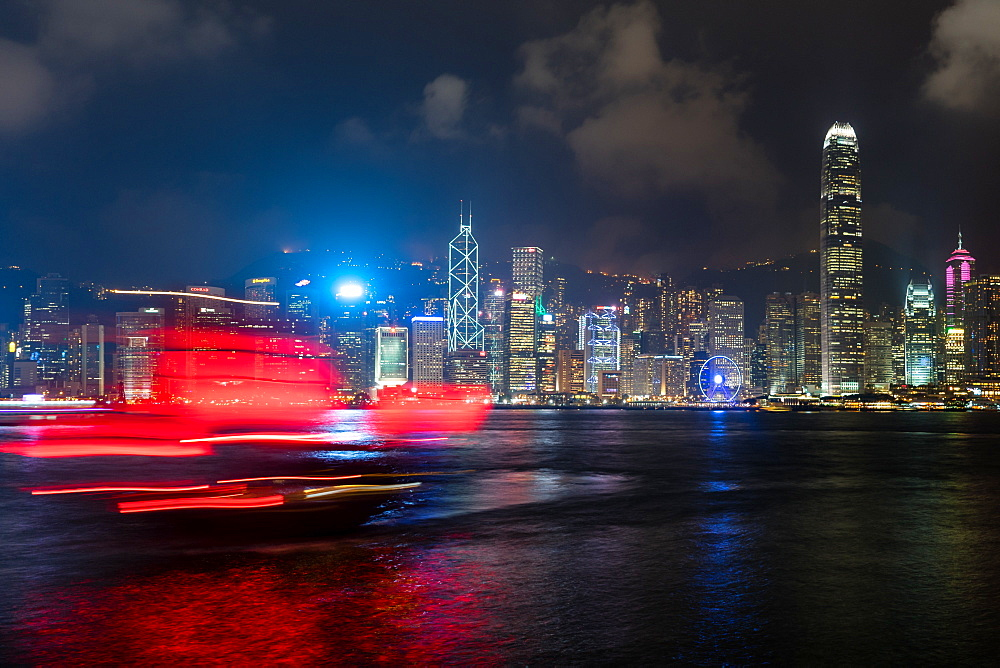 A red junk sailboat glides in front of the Hong Kong skyline at night, Hong Kong, China, Asia