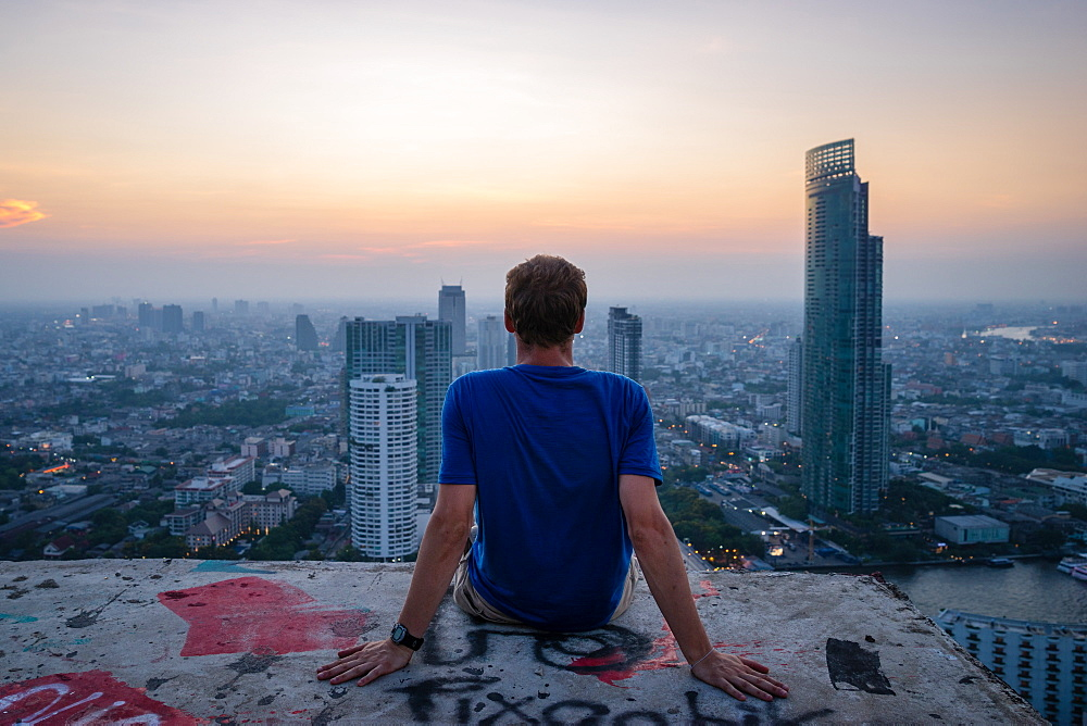 A single man watching sun set over city skyline at dusk, Bangkok, Thailand, Southeast Asia, Asia