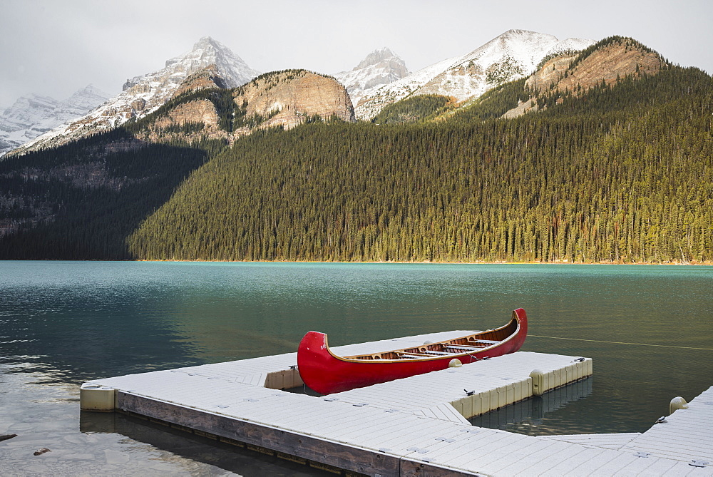 Red canoe and dock in Lake Louise with snow-covered mountains, Banff National Park, UNESCO World Heritage Site, Alberta, The Rockies, Canada, North America - 1241-106