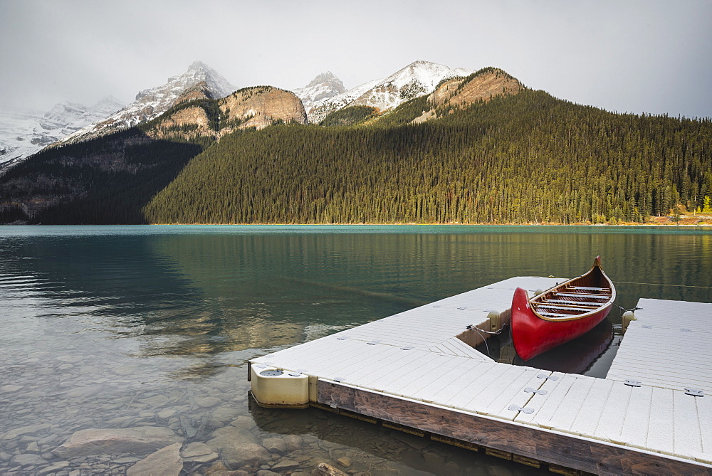 Red canoe and dock in Lake Louise with snow-covered mountains, Banff National Park, UNESCO World Heritage Site, Alberta, The Rockies, Canada, North America - 1241-108