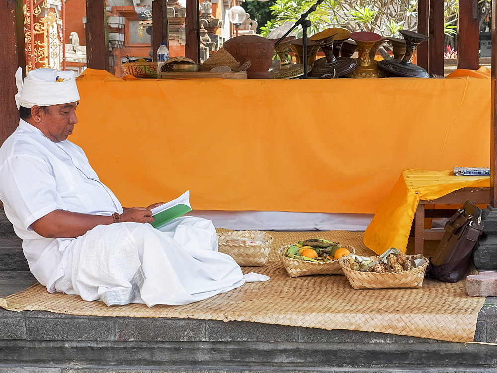 Man relaxing in a temple, Denpasar, Bali, Indonesia, Southeast Asia, Asia