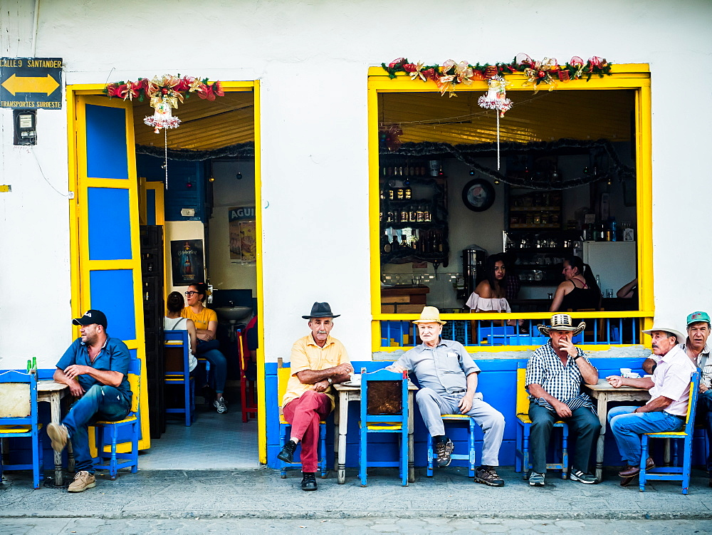 Men sit outside a bar, Jardin, Antioquia, Colombia, South America