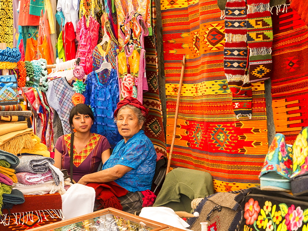 Women talking in market with background of handmade rugs and clothing, Oaxaca, Mexico, North America