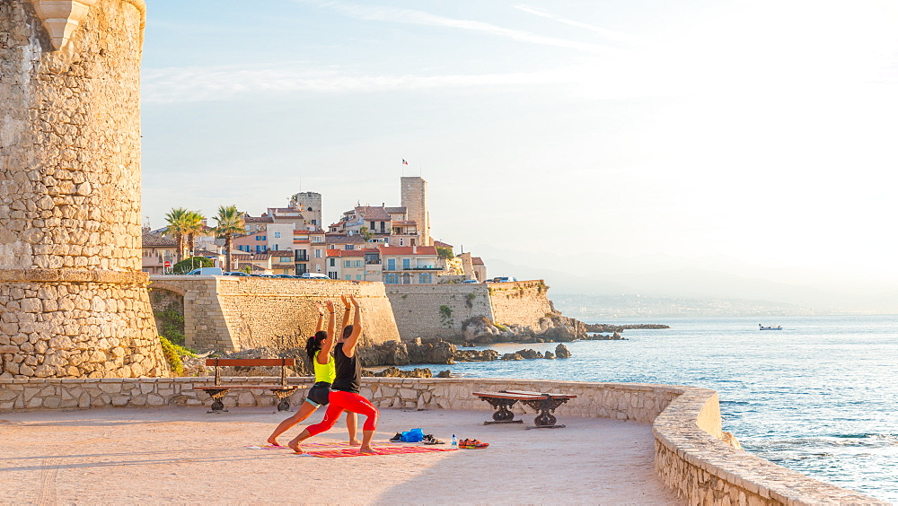A man and a woman practice yoga early in the morning overlooking Antibes, Cote d'Azur, France