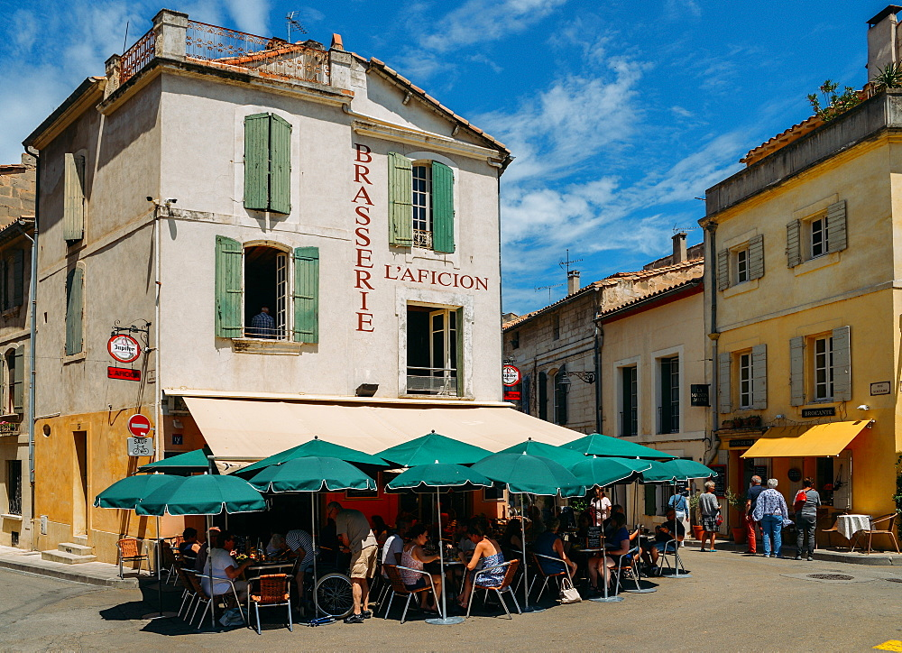 Tourists sit at an outdoor terrace in the historic centre of Arles, Bouches-du Rhone, Provence, France, Europe