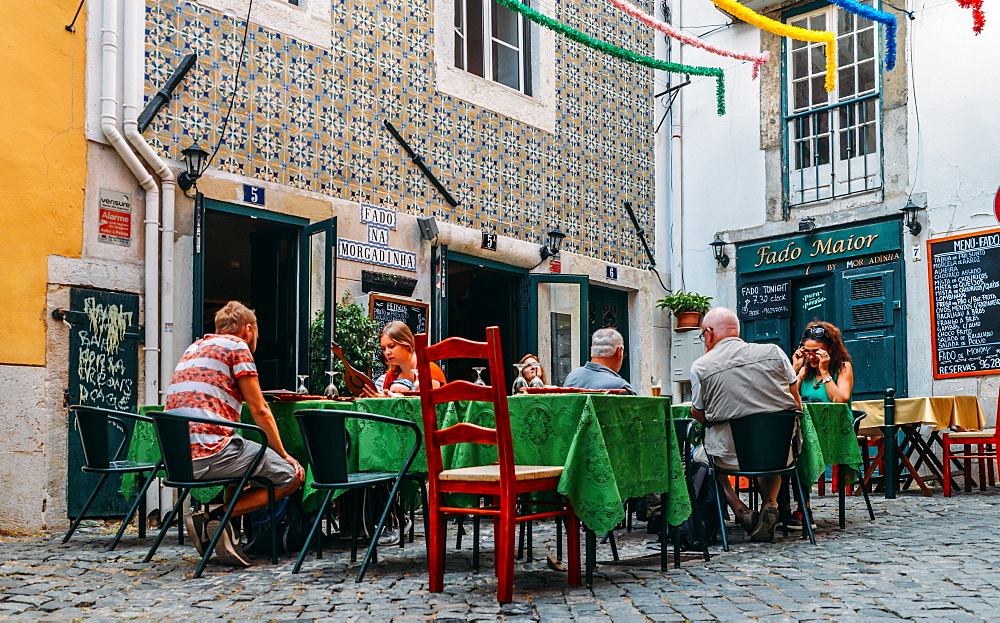 Tourists on a terrace of a restaurant serving traditional Portuguese food in the old district of Alfama, Lisbon, Portugal, Europe