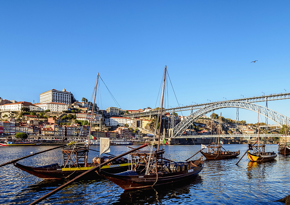 Traditional boats on Vila Nova de Gaia bank of Douro River, Dom Luis I Bridge in the background, Porto, Portugal