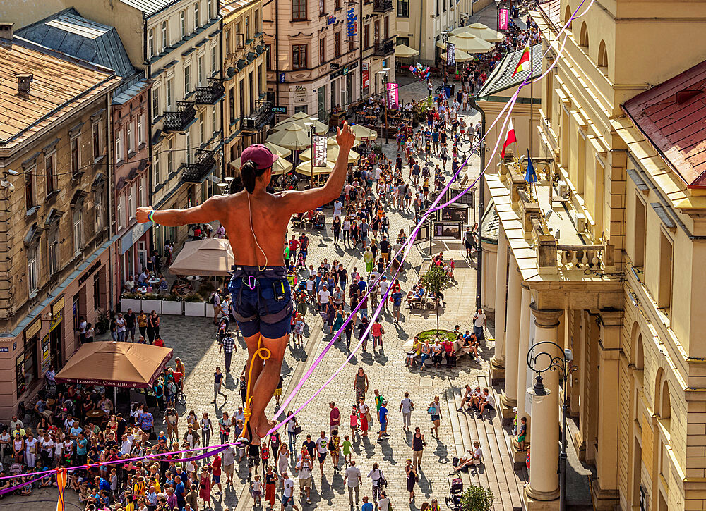 Man highlining with City Hall and Krakowskie Przedmiescie Promenade in the background, Urban Highline Festival, Lublin, Poland