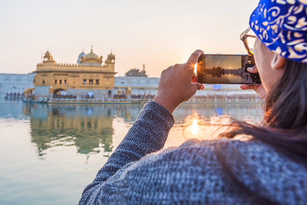 December 2018 - The Golden Temple in Amritsar, India. An Indian lady takes a smartphone picture of the Golden Temple at sunset