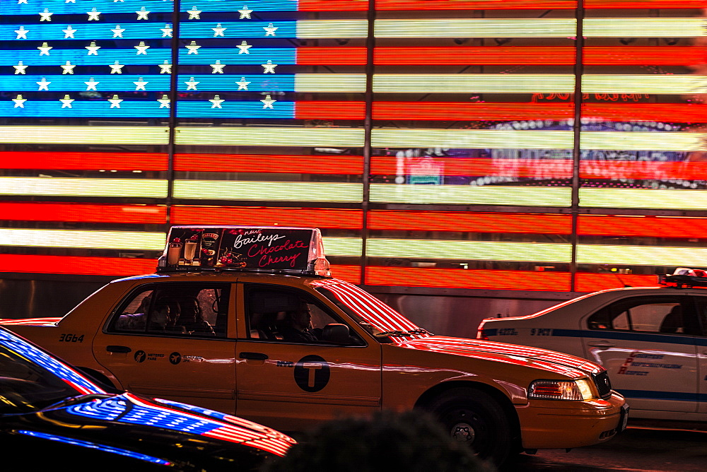 Yellow New York taxi in front of the American flag in Times Square, New York City, United States of America, North America