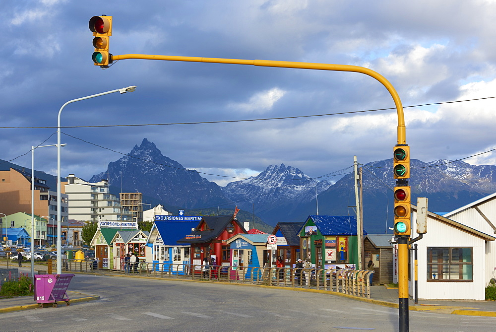 Colourful houses on touristic road framed by traffic lights post with snowy mountain chain beyond, Ushuaia, Argentina, South America