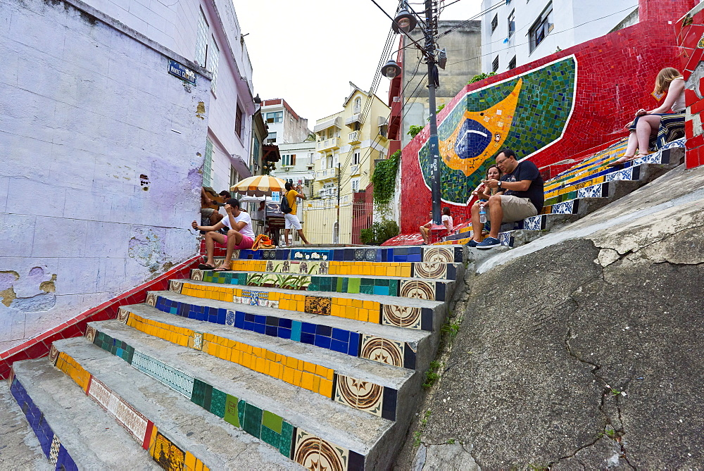 Tourists sitting on Selaron Steps, 215 decorated steps the work of artist Jorge Selaron, Rio de Janeiro, Brazil, South America