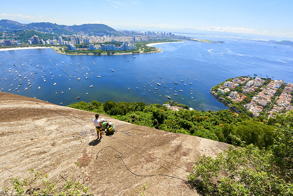 Abseilers in Morro da Urca in Rio de Janeiro with panoramic view in the background, Rio de Janeiro, Brazil, South America