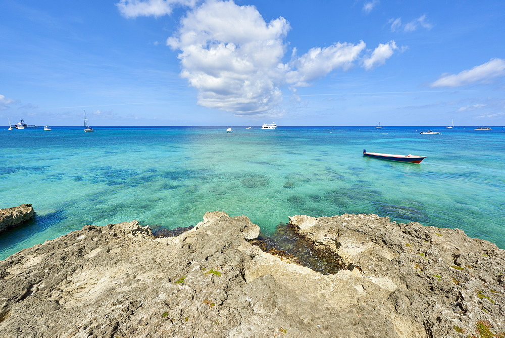 Rocky coastline in Cayman Islands with fishing boat in the transparent blue water.