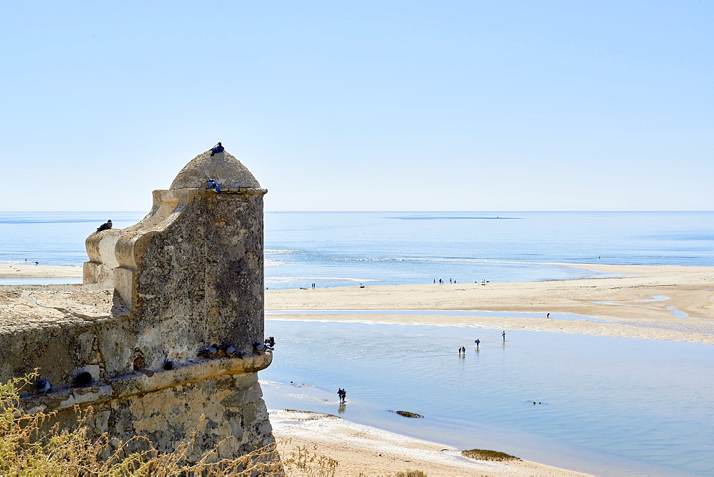 Detail of a watchtower in Cacela Velha, in Algarve, Portugal, with beachgoers crossing a lagoon formed by the low tide.